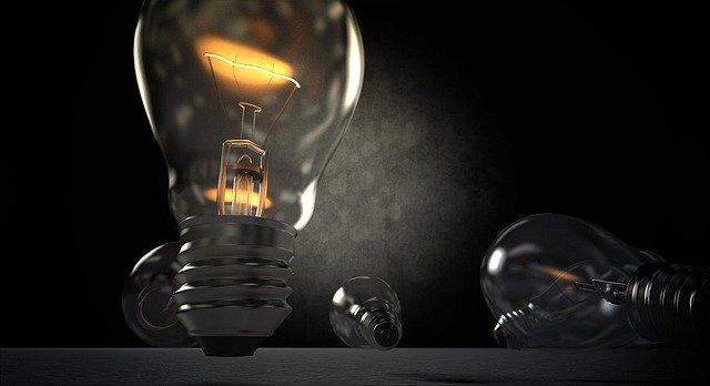 rozsvícená klasická žárovka a dvě nerozsvícené